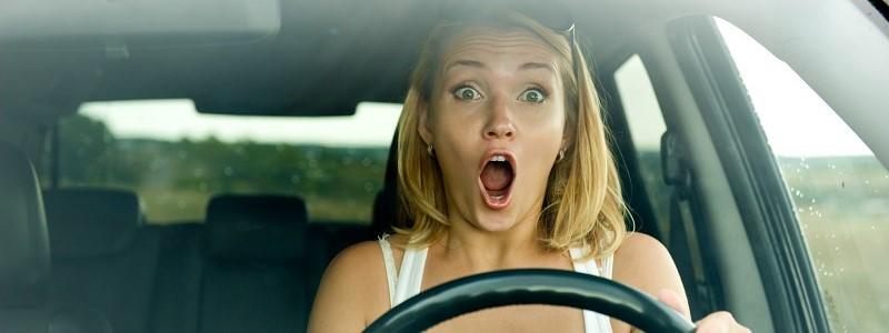 vrouw in auto ervaart afleiding in verkeer