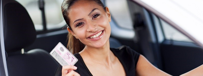 dame in auto met kentekenbewijs in de hand