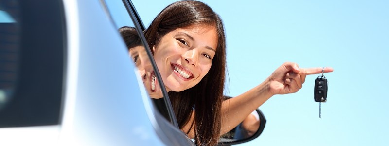 vrouw in auto met rijgedragverzekering en rijstijlpolis